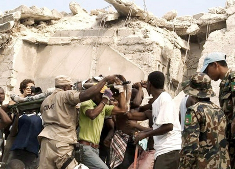 People carry an injured person after the earthquake in Port-au-Prince,